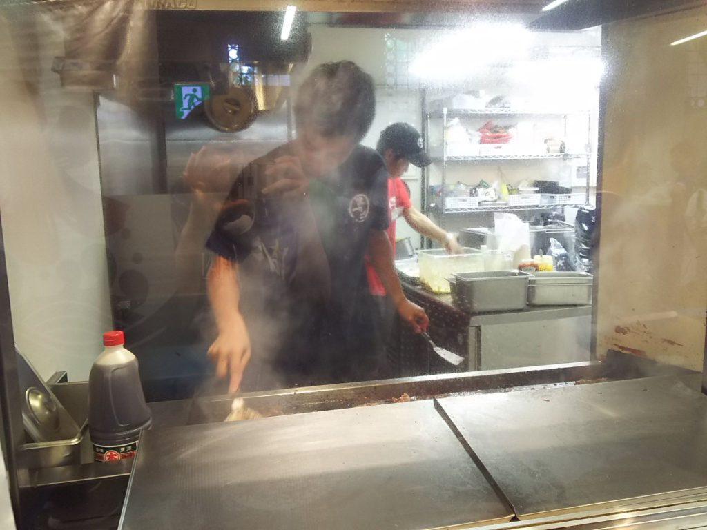 シースルーのガラス超しにお兄さんが鉄板で肉を焼いています