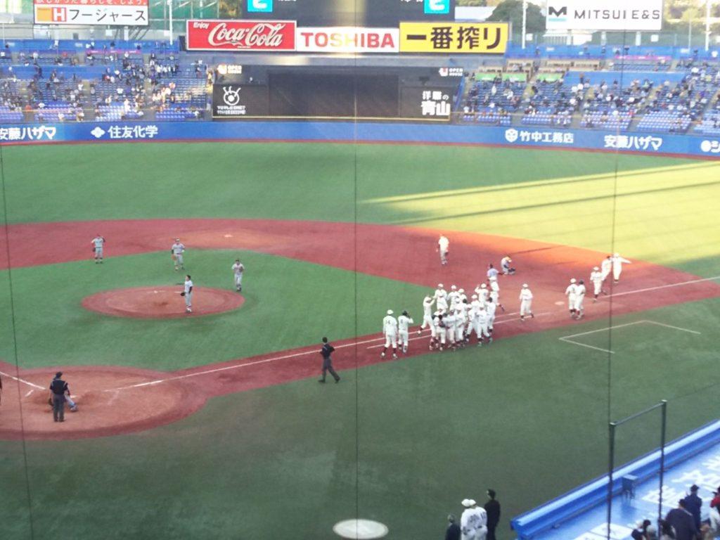 サヨナラ勝ちに沸く早稲田の選手とマウンドで呆然と立ち尽くす慶応・津留崎